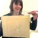 Librarian Caitlin McGurk holding an original drawing from Disney's 1940 Fantasia